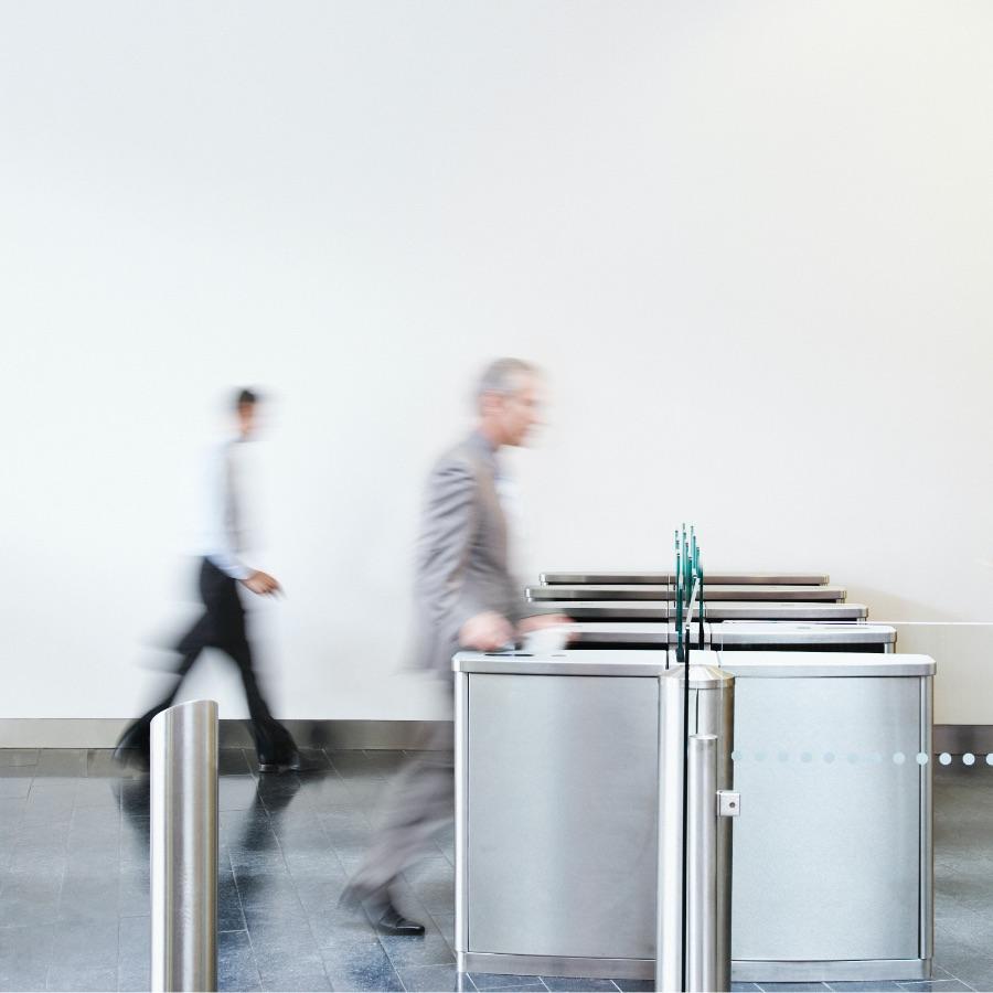 Two people walking through gates at train station