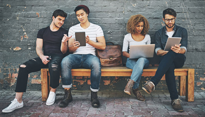 Four people sitting on a bench looking at laptops and iPads