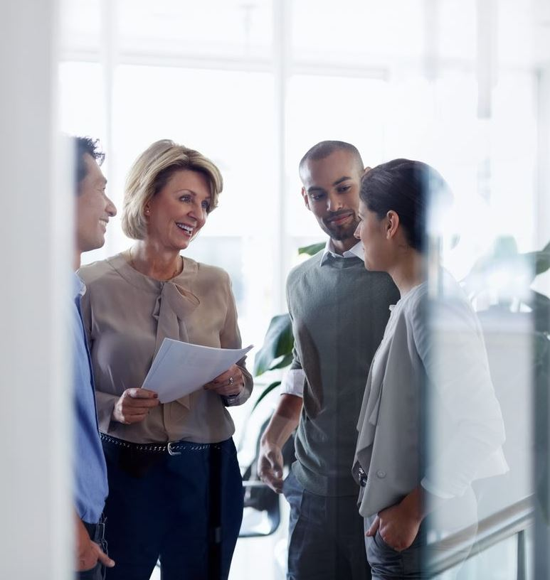 Group of people standing and talking in office