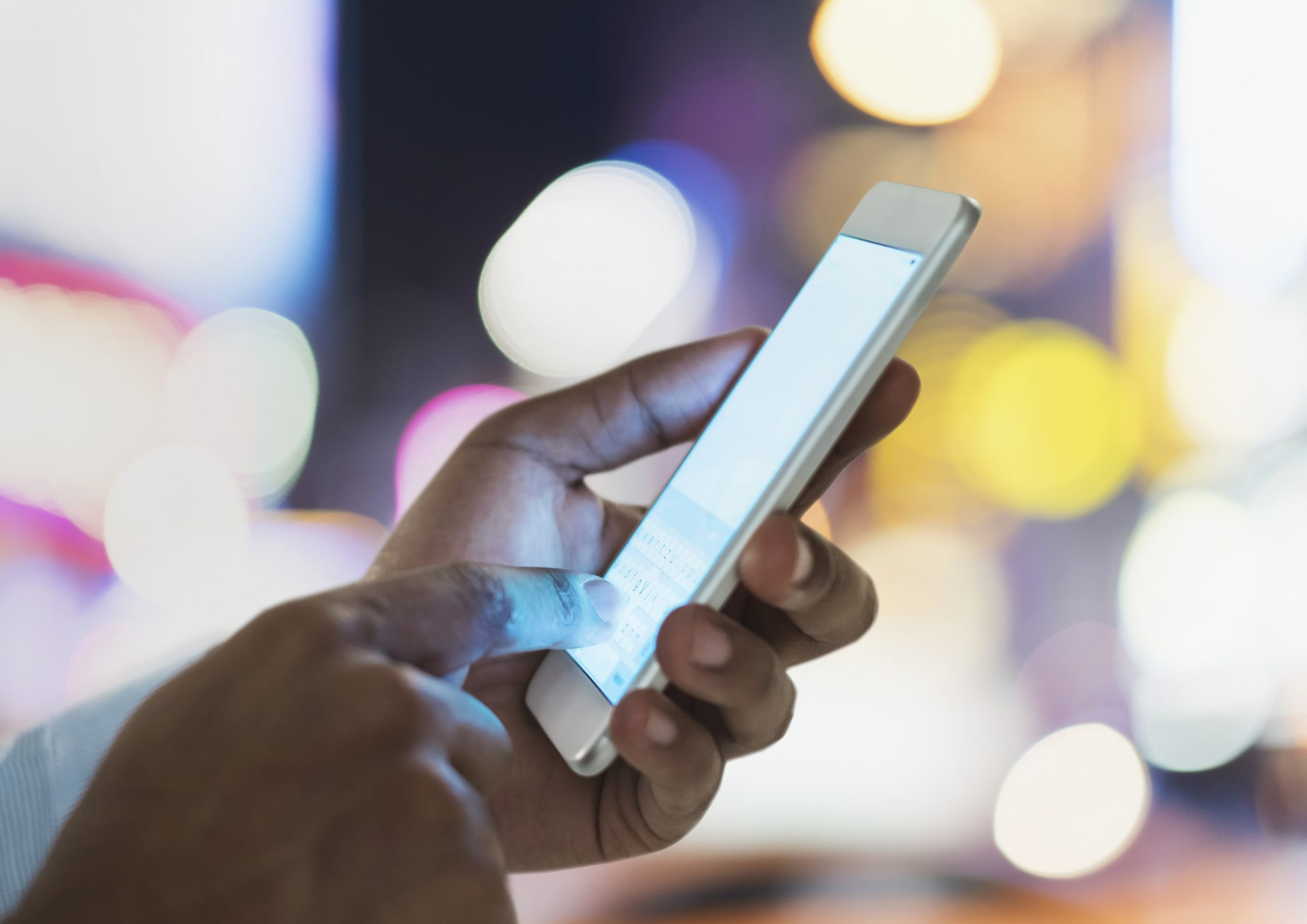 Person using mobile phone at night in city, close up