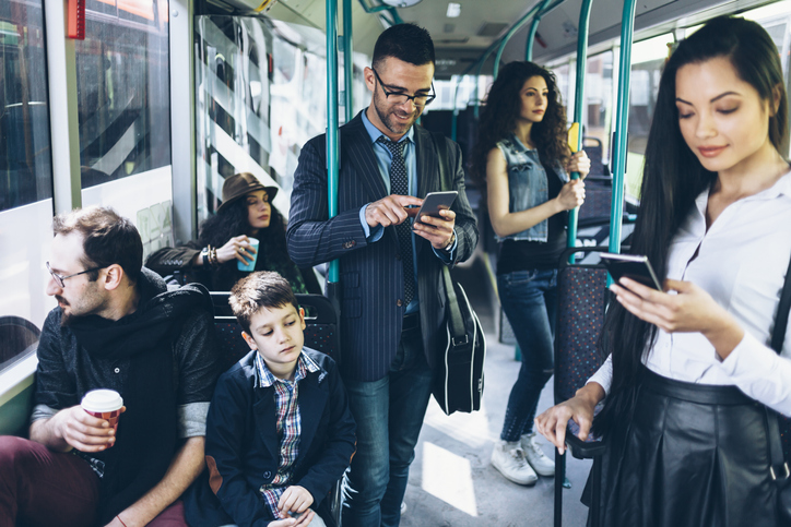 People on bus using mobile phones